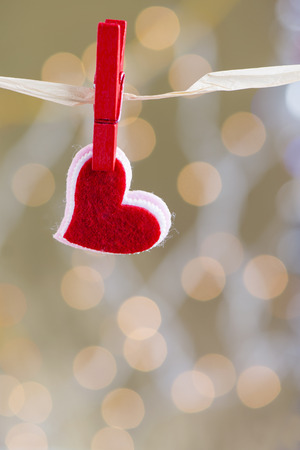 Love Valentines heart natural cord and red clip hanging over beautiful background