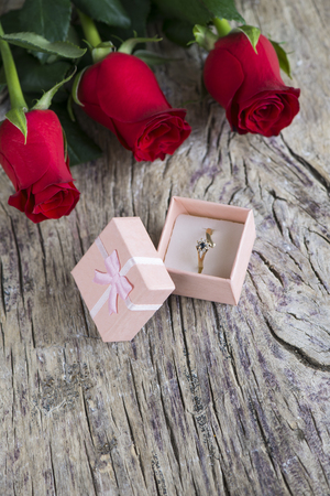wedding ring with red roses on textured wood Stock Photo