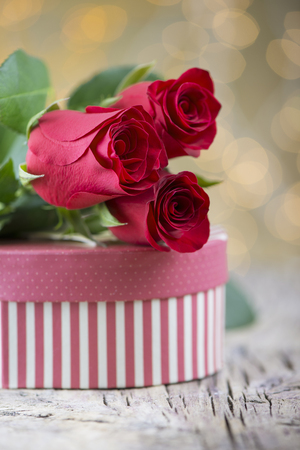 Beautiful red roses with present and petals on textured wood