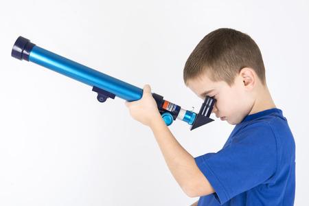 young boy looking trough telescope