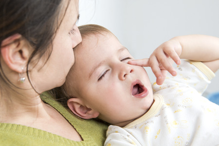 bedding indoors: Mother kissing her sleepy ill baby Stock Photo