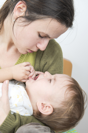 bedding indoors: Mother holding crying baby with flu