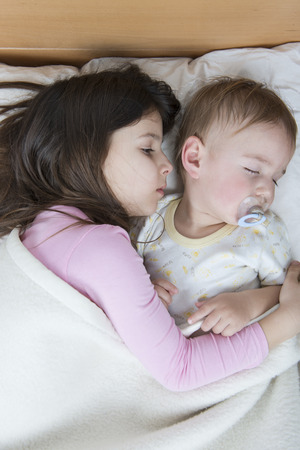 bedding indoors: sister calming her sick baby brother Stock Photo