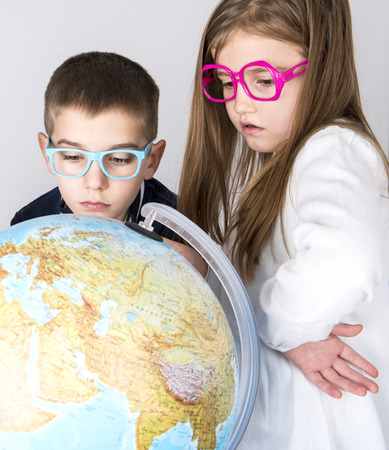 Two preschool kids looking at globe Stock Photo