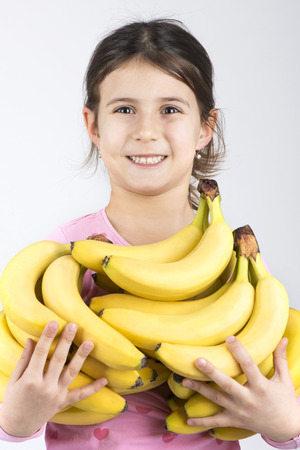 Smiling cute girl holding pile of bananas Stock Photo