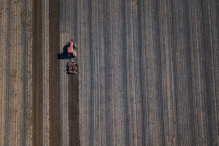Farmer working on field with tractor Stock Photo