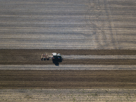 Harrowing field with tractor Stock Photo