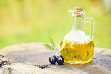 Oliven und Öl in der Flasche auf altem strukturiertem Holz Standard-Bild