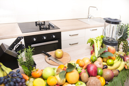 using juicer to prepare fresh healty drinks in kitchen Stock Photo