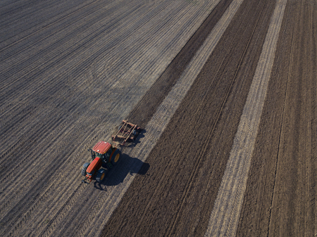 Farmer working with automated GPS coordinated tractor on field