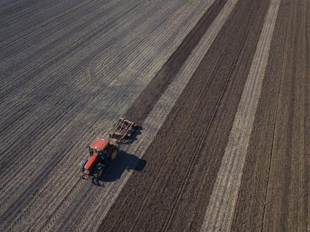 Granjero que trabaja con el tractor coordinado GPS automatizado en el campo Foto de archivo