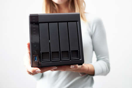 girl person hold in hands portable office or home data nas server. device for backup important information. copy space.