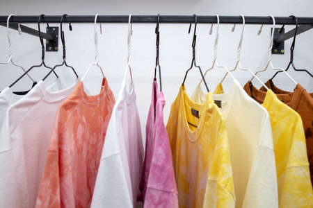 fashion casual t-shirts hanging at store place. colorful choice for buy clothes