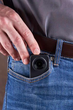 hidden photo or video camera at jeans pocket. harassment and blog concept
