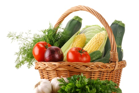 veganism: Composition with fresh vegetables and wicker basket isolated on white