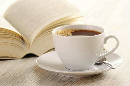 Composition with cup of coffee and book on the table photo