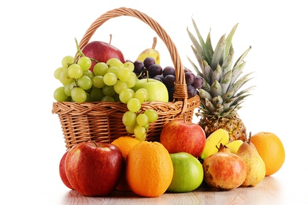 Wicker basket with fruits isolated on white photo