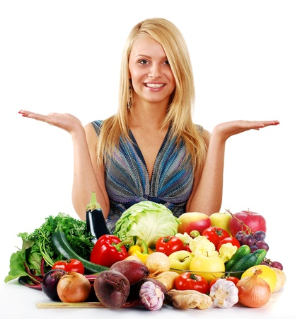 veganism: Young blond woman standing at the table with variety of fresh raw vegetables  Stock Photo