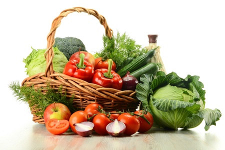 veganism: Composition with raw vegetables and wicker basket isolated on white