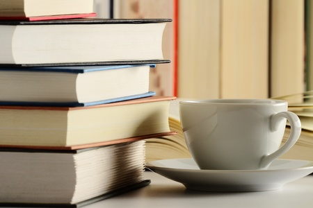 Composition with books and cup of coffee on the table photo