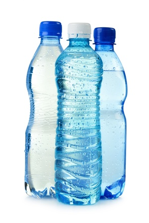 Three polycarbonate plastic bottles of mineral water isolated on white photo