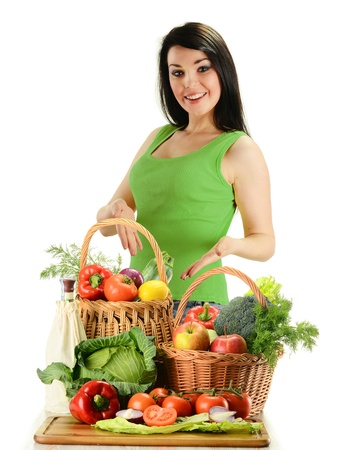 Young smiling woman standing at the table with variety of fresh raw vegetables in wicker baskets isolated on white  photo