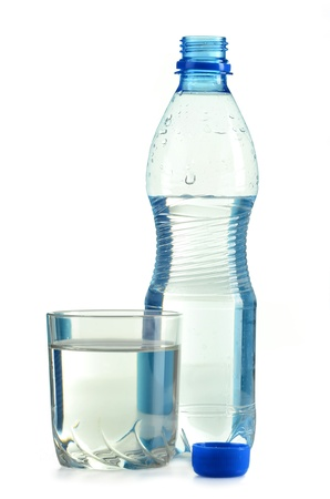 Polycarbonate plastic bottle of mineral water and glass of water isolated on white photo