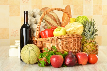 Groceries in wicker basket on kitchen table photo