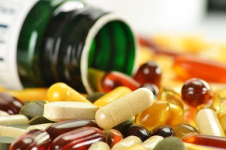 Composición con las cápsulas de suplementos dietéticos y los contenedores. Variedad de pastillas de drogas Foto de archivo