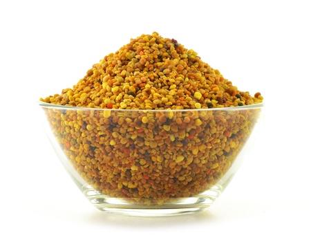 bee pollen: Kom met bijenpollen geïsoleerd op wit. Voedingssupplement