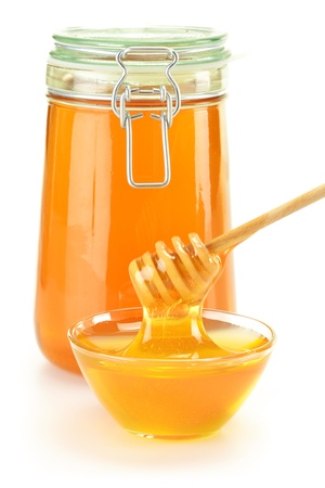 Composition with dish of honey and stick isolated on white Stock Photo - 10221449