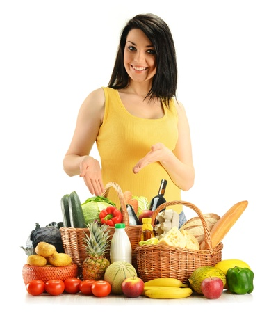 bakery products: Young woman with groceries in wicker basket isolated on white Stock Photo