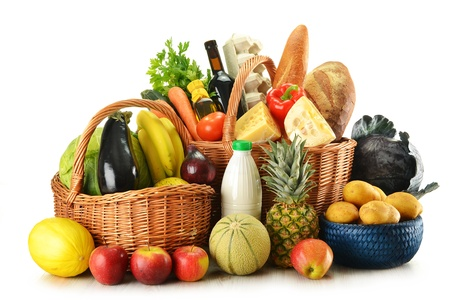 Groceries in wicker basket isolated on white photo