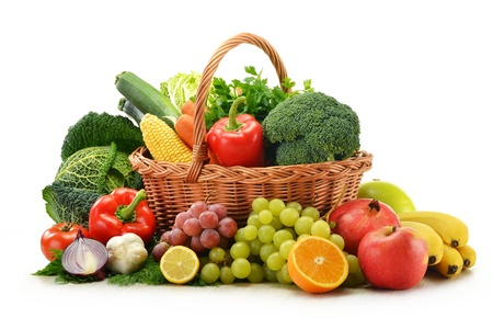 fruitmand: Compositie met groenten en fruit in rieten mand op wit wordt geïsoleerd