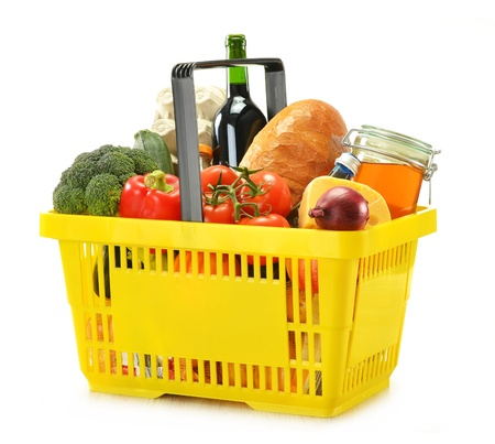 Composition with shopping basket and groceries isolated on white photo