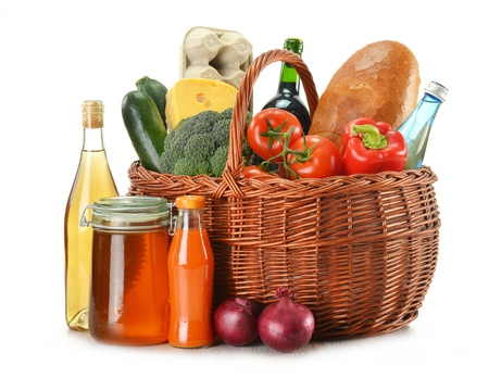 Grocery in wicker basket isolated on white  photo
