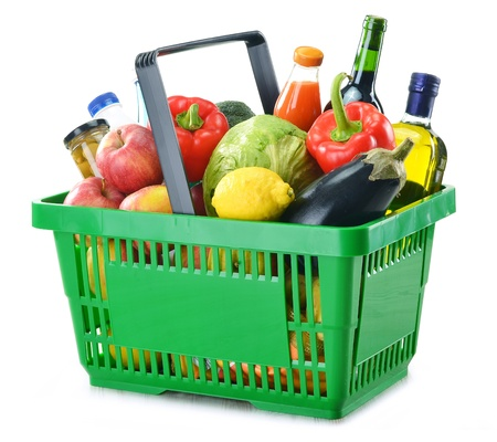 Green shopping basket with variety of grocery products including vegetables, fruits and wine isolated on white