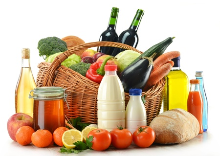 Composition with raw food including vegetables, fruits, bread and wine presented in wicker basket isolated on white