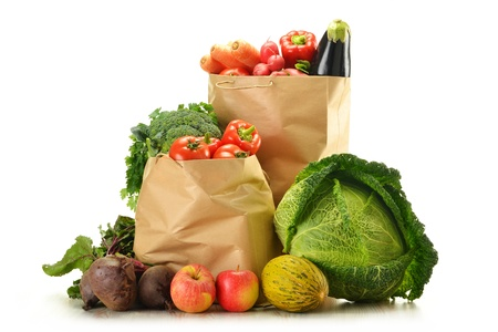 Composition with raw vegetables and shopping bag isolated on white