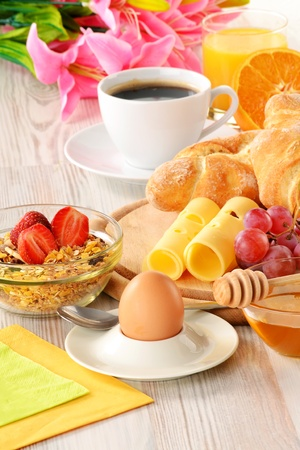 Breakfast with coffee, rolls, egg, orange juice, muesli and cheese photo