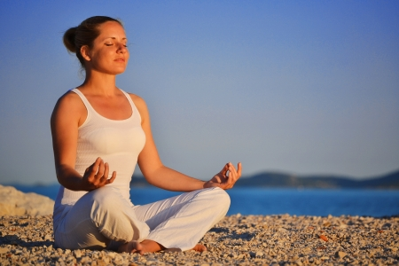 Young woman during yoga meditation on the beach Stock Photo