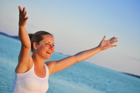 Young woman with hands up expressing joy on the beach  photo