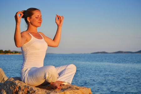 Young woman during yoga meditation on the beach photo
