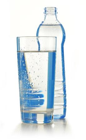 copa de agua: Vidrio y botella de agua mineral aislado en blanco
