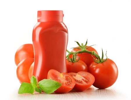Komposition mit Ketchup-Flaschen und Tomaten isoliert auf wei?