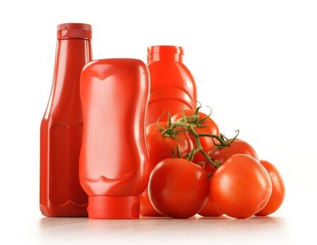 salsa de tomate: Composición con botellas de salsa de tomate y tomates aislados en blanco Foto de archivo