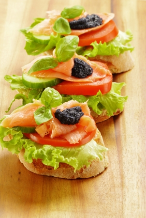 Three sandwiches with salmon and caviar  Fish snack photo