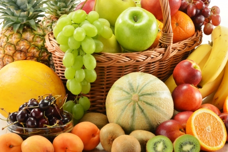 fruits in a basket: Composition with assorted fruits in wicker basket isolated on white