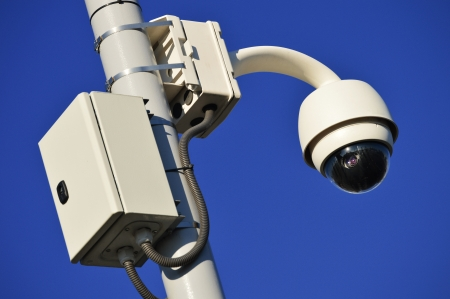 private security: Hi-tech dome type camera over a blue sky