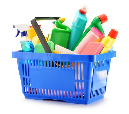 Cesta de la compra con botellas de detergente de limpieza e insumos químicos aislados en blanco
